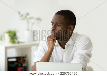 Young African-american Thoughtful Businessman Holding Hand On Chin Planning Future Project At Work W