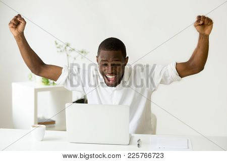 Excited Euphoric African Winner Looking At Laptop Celebrating Online Win Success Achievement Result,