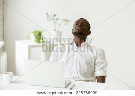 African Office Worker Relaxing With Eyes Closed Sitting At Work Desk With Laptop, Black Employee Tak