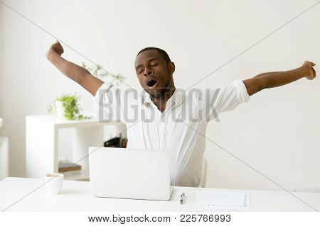 Sleepy African American Man Stretching Yawning At Workplace, Tired Black Lazy Worker Feels Lack Of S
