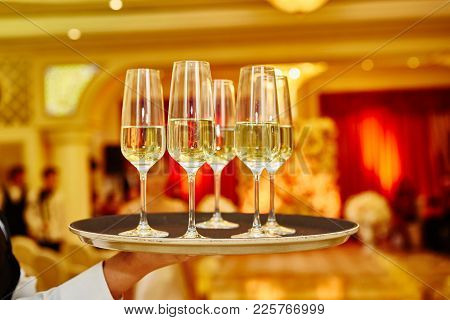 Waiter Serving Champagne On A Tray. Full Glasses Of Champagne On Tray