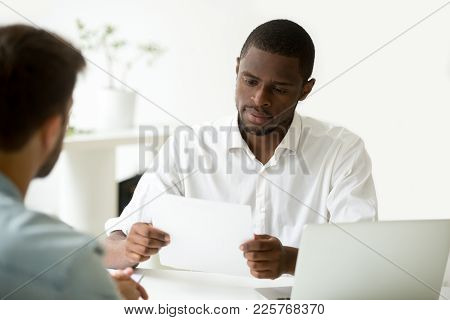 Serious African Businessman Reading Document At Meeting, Black Entrepreneur Considering Contract, Co