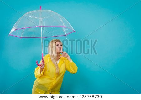 Blonde Woman Wearing Yellow Raincoat Holding Transparent Umbrella Checking Weather If It Is Raining