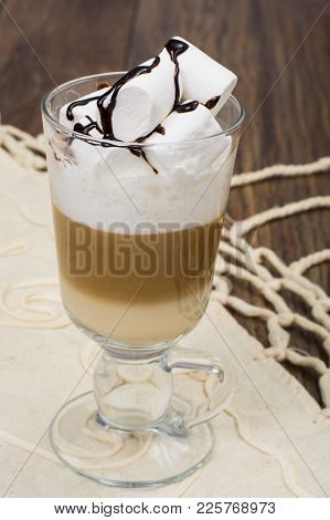 Tall Glass With Latte And Marshmallow On Wooden Table. Studio Photo