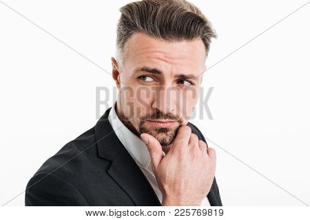 Photo of attractive brunette businessman in formal wear looking aside with brooding look and touching his chin isolated over white background