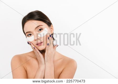 Beauty portrait of brunette asian womantouching her face while wearing cosmetic eyes patches isolated over white background
