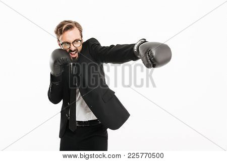 Portrait of decisive business man in black suit and eyeglasses emoionally punching aside in boxing gloves isolated over white background