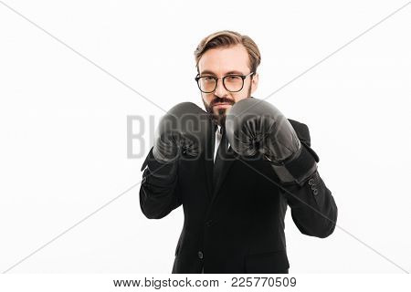Portrait of brunette man in black suit and eyeglasses looking on camera and posing in boxing gloves isolated over white background