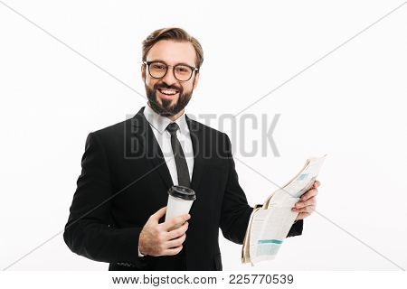 Portrait of cheerful male employer in suit and eyeglasses smiling while drinking takeaway coffee and reading newspaper isolated over white wall