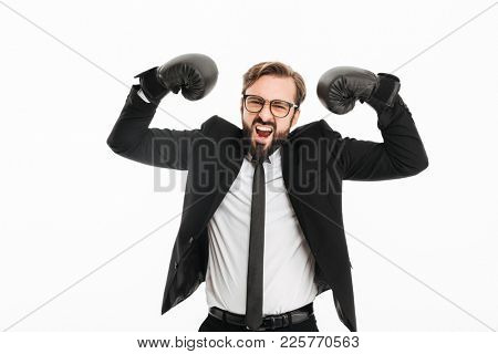 Photo of delighted businessman in black suit and eyeglasses rejoicing his vicory in boxing gloves isolated over white background