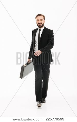 Full-length image of confident ambitious man in business suit walking with black briefcase and looking on camera isolated over white background