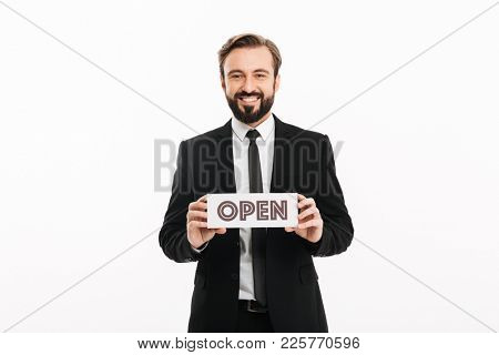 Portrait of cheerful male employer smiling and holding banner with word open on camera isolated over white background