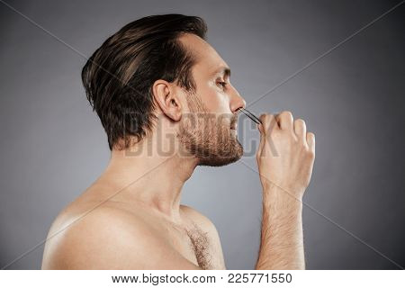 Side view portrait of a handsome man removing nose hair with tweezers isolated over gray background