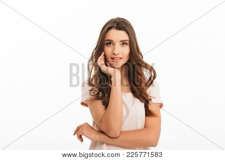 Sensual smiling brunette woman in t-shirt reclines on her arm and looking at the camera over white background