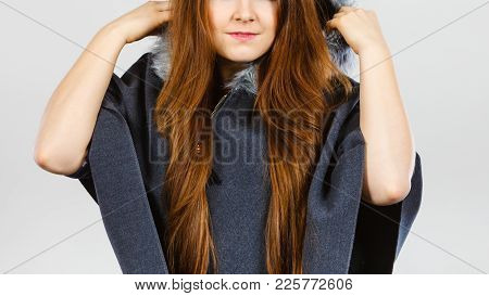Happy Woman Wearing Dark Poncho With Furry Hood. Winter Fashion, Trendy Clothing Outfits Concept.