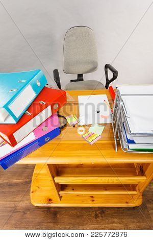 Wooden Desk Full Of Colorful Ring Binders With Documents And Files With Gray Office Chair. High Angl