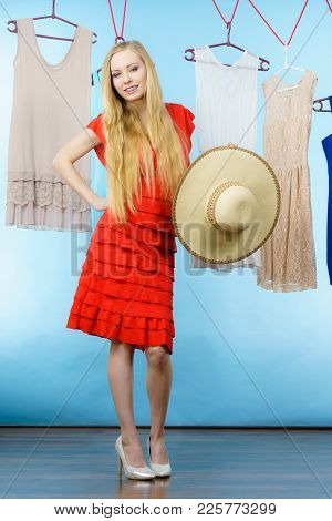 Woman In Clothes Shop Store Picking Summer Perfect Outfit, Holding Big Hat, Dress Hanging On Clothin