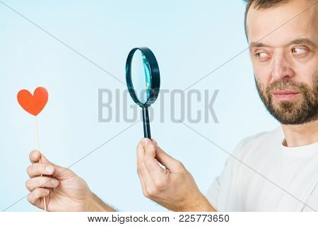Uncertain Man Looking At Love Little Heart Shape On Stick Using Magnifying Glass Thinking About Roma