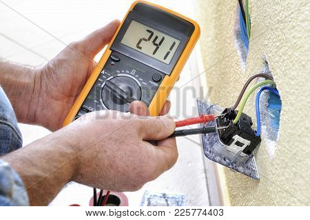 Electrician Technician At Work Measures The Voltage Of A Residential Electrical System
