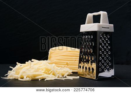 Grater And Cheese On Dark Slate Background With Copy Space, Close-up