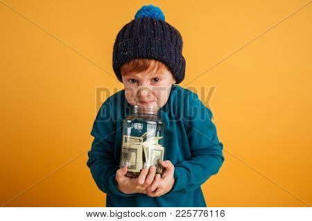 Image of angry displeased little redhead boy with freckles standing isolated over yellow background wearing warm hat. Looking camera holding jar with money.