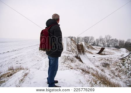 Middle Age Man Standing In Beautiful Winter Landscape . Man Viewing On Abandoned Freestyle Motocross