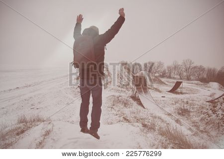 Middle Age Man Jumping  In Beautiful Winter Landscape . Man Viewing On Abandoned Freestyle Motocross