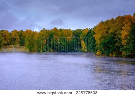 The River Flows Through The Autumn Forest. Autumn Landscape - The River Flows Through The Autumn For