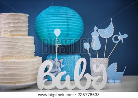 Yummy cake and decorations for baby shower party on table near color wall poster