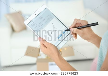 Woman appending signature after receiving parcel indoors