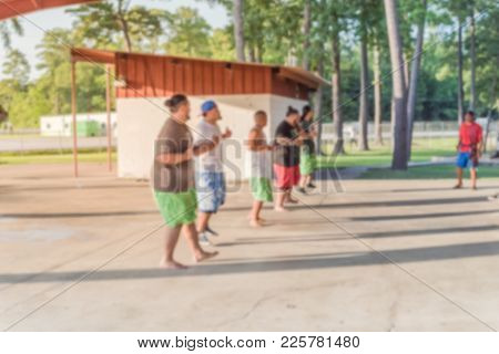 Blurred group of men performing traditional Samoan dances at public Park in USA. This dance form has been adopted, adapted through western Polynesia, in the Kingdom of Tonga, Uvea, Futuna, Tokelau poster