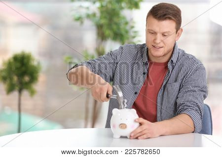 Young man holding hammer over piggy bank at home