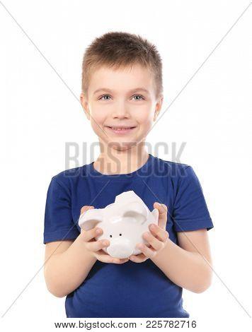 Cute boy holding broken piggy bank on white background