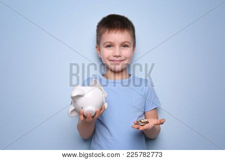 Cute boy holding broken piggy bank and coins on color background
