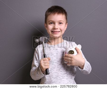 Cute boy holding hammer and piggy bank on grey background