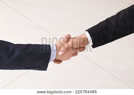 Two man shaking hands as symbol of unity on light background