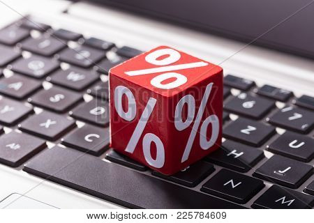 Close-up Of Percentage On The Red Wooden Block Over The Laptop Keypad