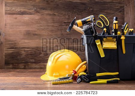 Close-up Of Safety Helmet With Tools In The Black Container On The Wooden Table
