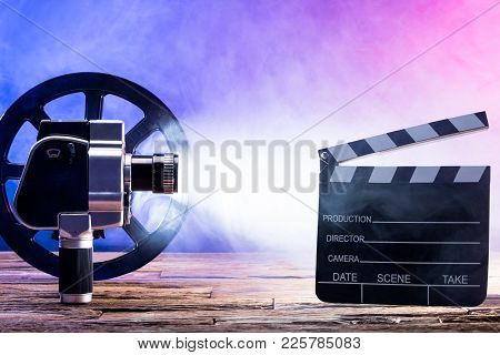 Close-up Of An Illuminated Movie Camera With Film Reel And Clapper Board On Wooden Desk