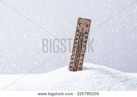Thermometer On Snow Showing Low Temperature In Heavy Snowfall