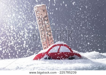 Red Car Covered With Snow In Front Of Thermometer During Heavy Snowfall