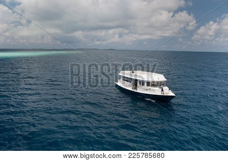 White Ship For Drivers, Floating Among The Waters Of The Indian Ocean, In The Background Reef Atoll,