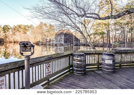 A rustic grainy view of Yates Mill Pond from a wooden viewing deck with recycling barrells.