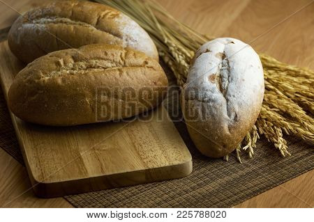 Fresh Bread On Brown Wooden Table Background.