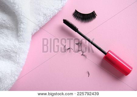 Mascara and false eyelashes on color background