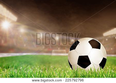 Soccer Ball On Field Grass In Brightly Lit Outdoor Stadium With Focus On Foreground And Shallow Dept