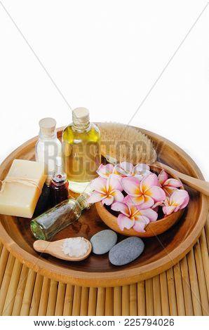 Set of soap.salt ,spoon, frangipani ,stones,brush ,bottle oil in wooden bowl on mat