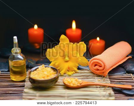 Spa setting with yellow orchid, set of candle, black stones,salt in spoon,oil on mat
