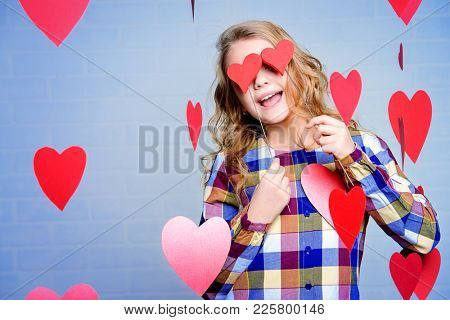Happy pre-teen girl closed her eyes with hearts and poses surrounded by hearts. First love. Valentine's Day.