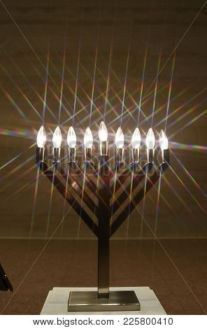 Hanukkah Menorah With Eight Illuminated Candle Stick Light Bulbs On A Pedestal. Jewish Religious Hol